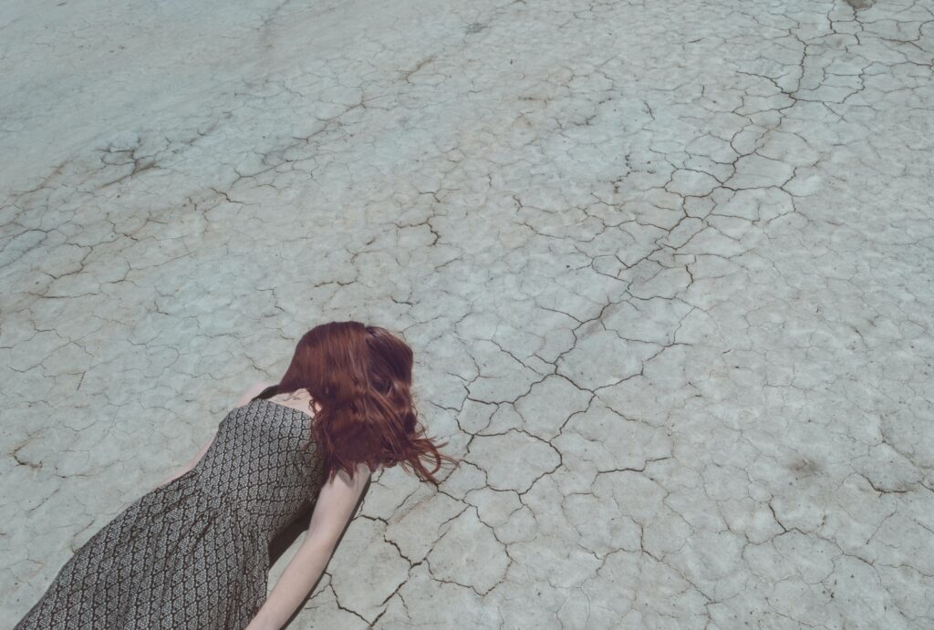 A girl with red hear lays face down in the grey dirt of a dried up lake, amongst mud cracks